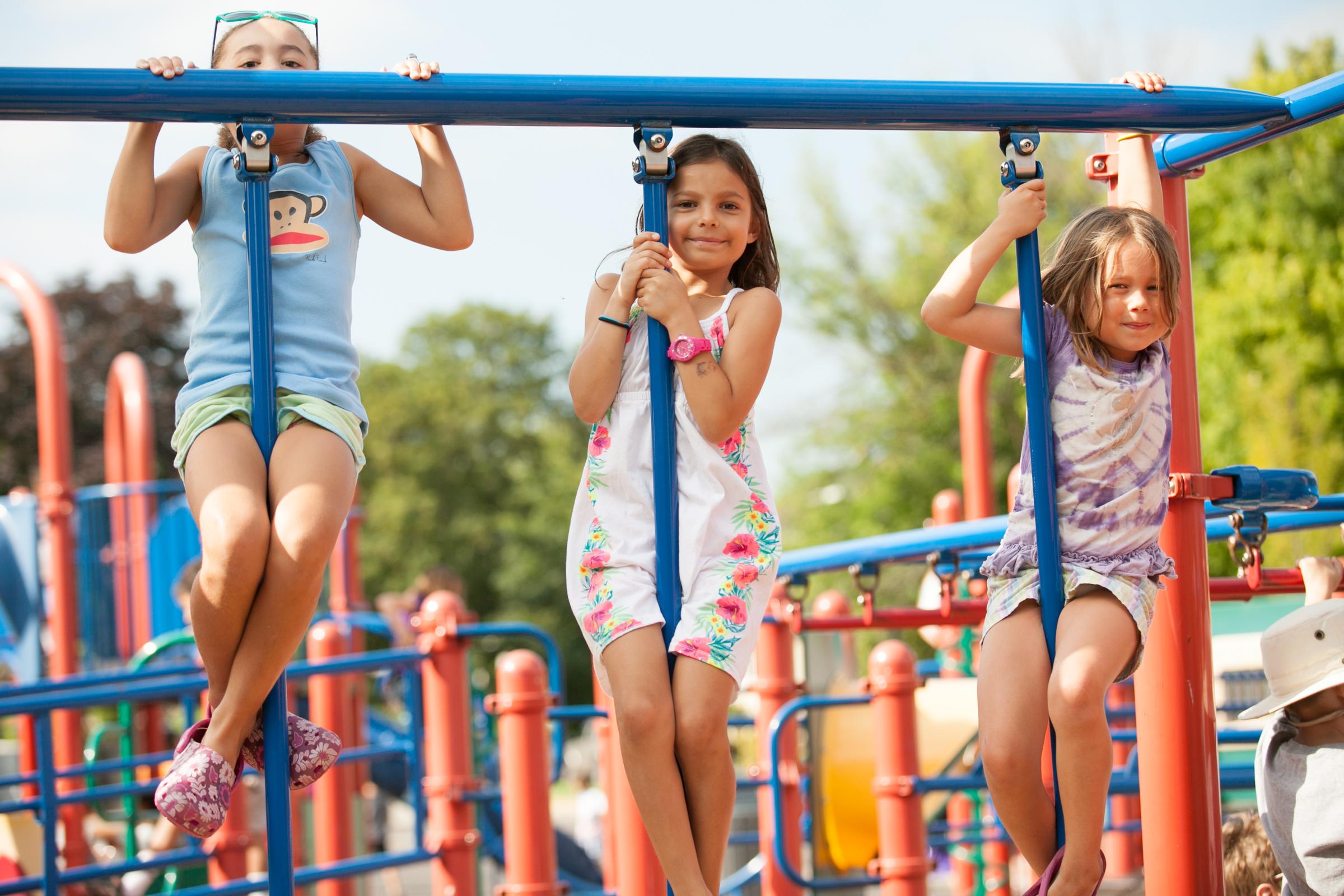 three girls on playground equipment